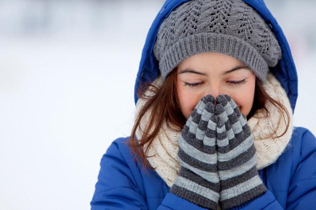 Chica con gorro gris y guantes rayados protegiéndose del frío