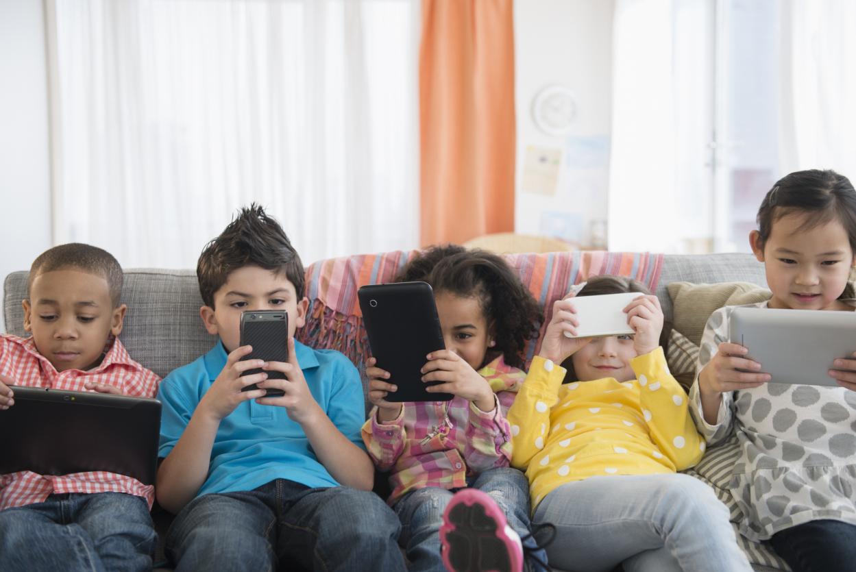 Cinco niños viendo sus dispositivos móviles al mismo tiempo