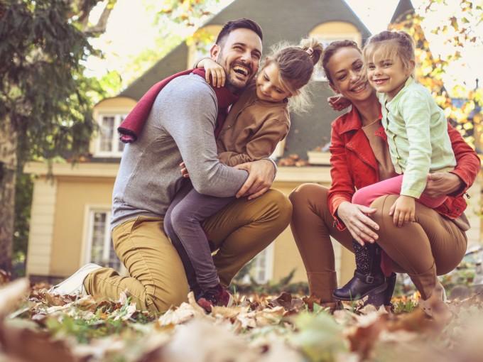 Familia abrazada en el patio de su casa y riendo.