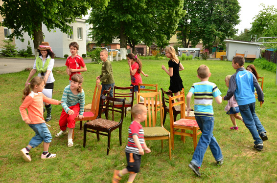 Niños jugando a las sillas en el patio trasero de una casa