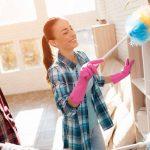 Pareja sacudiendo los muebles de su hogar
