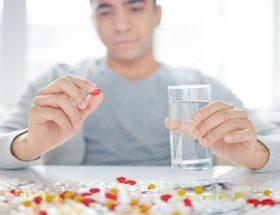 hombre tomando medicamentos Aurax