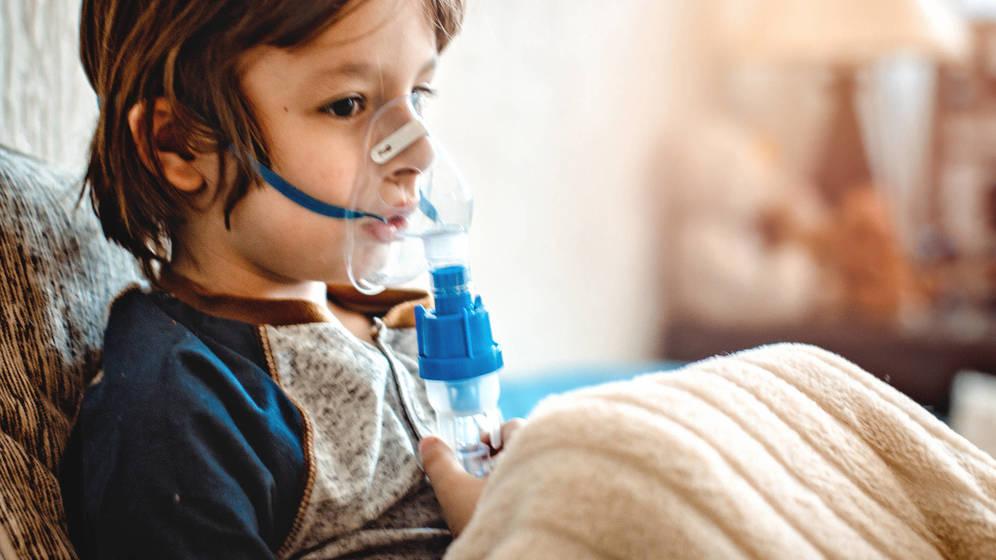 niño con su inhalador para el asma