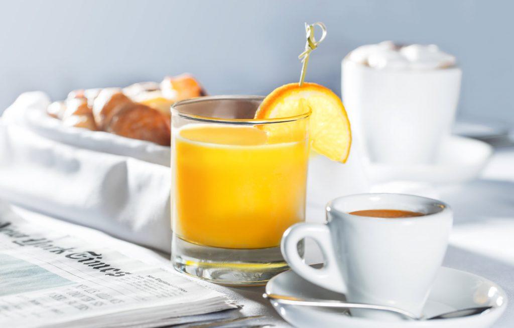 Mesa de desayuno con vaso de jugo y taza de café