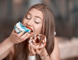 Mujer comiendo dos donas