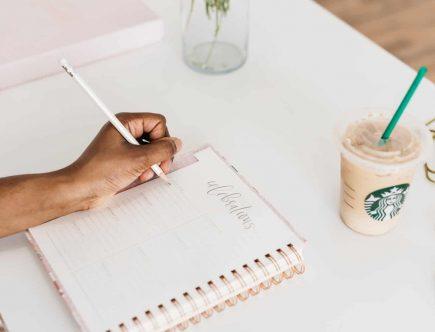 Persona estableciendo una rutina en un cuaderno en su área de trabajo