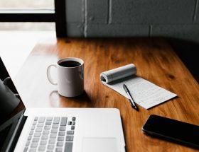 Escritorio con laptop, taza de café, cuaderno y pluma