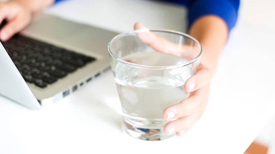Persona con un vaso de agua cerca de su área de trabajo